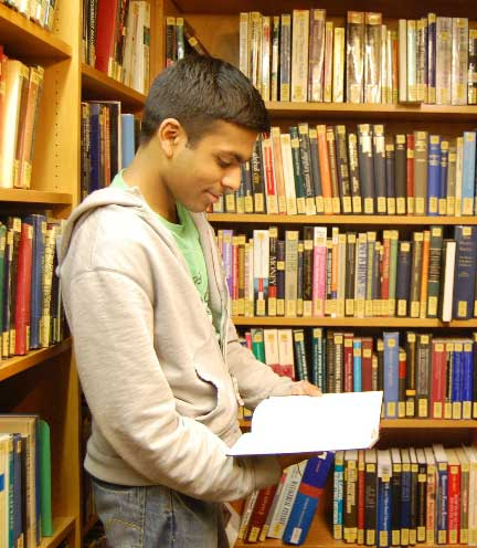 International Student Reading a book in a library